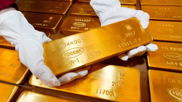 Руки в перчатках держат золотой слиток