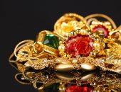 золотое украшение с разноцветными камнями
