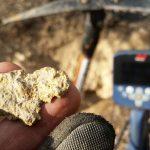 кусок золота и металлоискатель на фоне