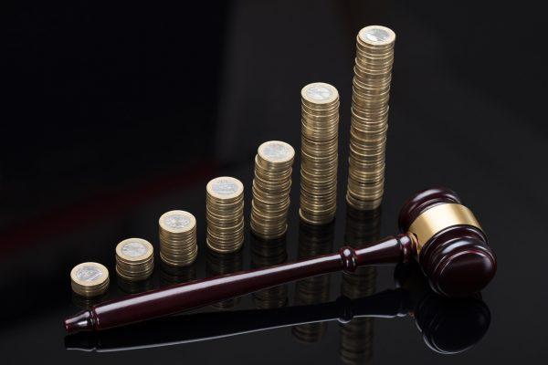 монеты, сложенные стопками, и судейский молоток